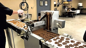 Enrobing machine coating pretzels with chocolate at Vermont Nut Free Chocolates