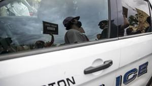 Demonstrators passing a police car in Burlington