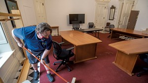 Custodian Mike Metcalf readying the coatroom at the Statehouse