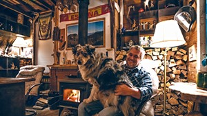Macao Bravo and his dog in his Winooski man cave