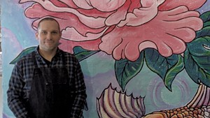 Brian Lewis in front of a mural by Tara Goreau at Filling Station