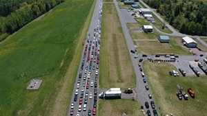 Cars line up to get food during a Farmers to Families Food Box drop last year