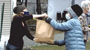 A Heineberg volunteer delivering a meal