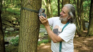 Steve Parren checking his game camera near the stream behind his home in Monkton