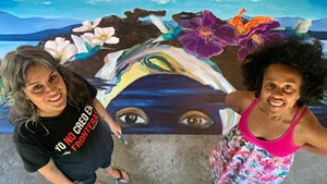 """Cynthia Cagle and Ferene Paris Meyer stand next to the mural """"Ferene Existing While Black"""""""