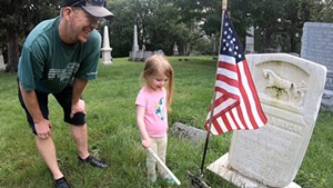 Jason Stuffle and his daughter Jimi install military markers at Greenmount Cemetery