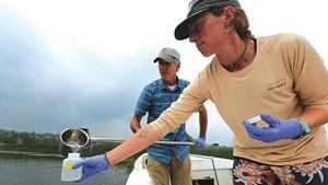 Rick Levey and Kelsey Colbert gathering water samples in Lake Memphremagog