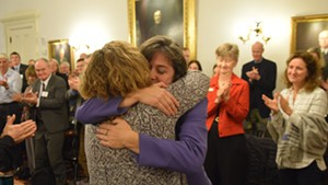 Reps. Mitzi Johnson, in purple, and Sarah Copeland Hanzas hug after Johnson won the vote to be the Democrats' nominee for House speaker.