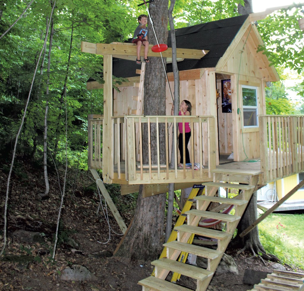 a backyard tree house with zip line and hammock gardens