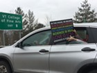 A person in a car stuck in I-89 traffic shows support