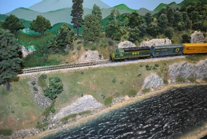 """The NWV Railroad's """"Local 501"""" rolls along the river bank on the Northwestern Vermont Model Railroad Association's HO-scale layout in Essex Junction. - Uploaded by NWV"""