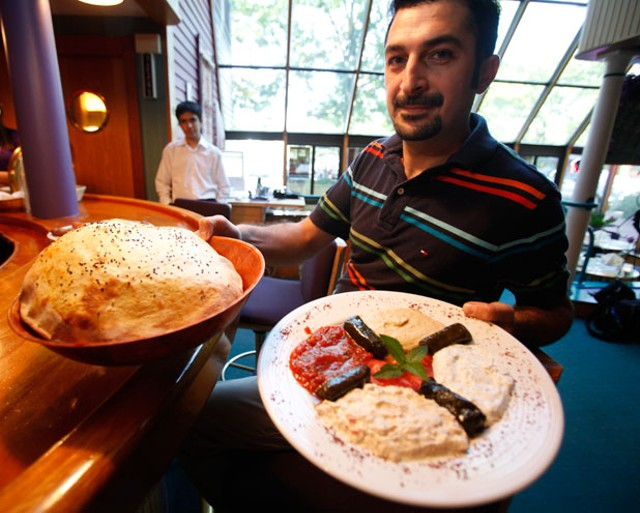 Vural Oktay holding lavash and a meze platter - JORDAN SILVERMAN