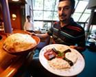Vural Oktay holding lavash and a meze platter