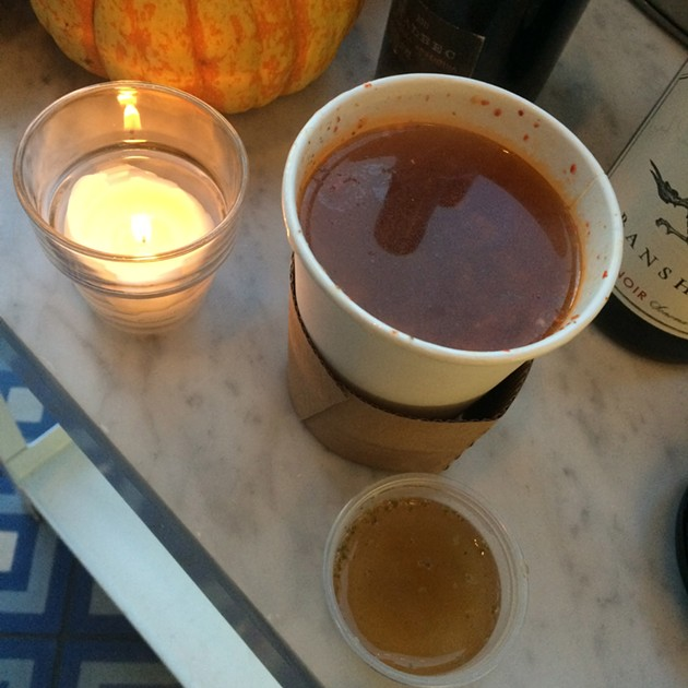 A cup of Belcampo's Calabrian chili broth, with a sample of the ginger-garlic-coriander version. - PETE KANE