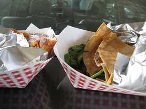 A parked car's hood serves as a table. - M. BRODY
