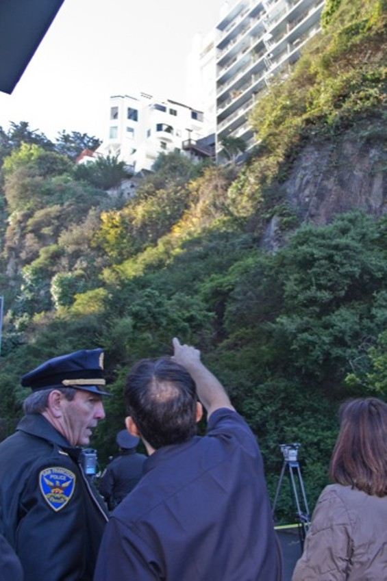 A police officer points in the general vicinity of the alleged burglar, who has clung to the side of the hill since Tuesday evening - JOE ESKENAZI