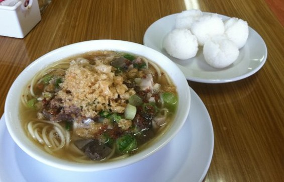A small bowl of La Paz Batchoy's noodle soup, with a side of puto (steamed rice buns). - JONATHAN KAUFFMAN