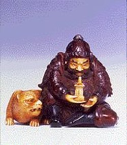 A wood and ivory netsuke featuring the - Japanese god - of wealth, happiness, and war.