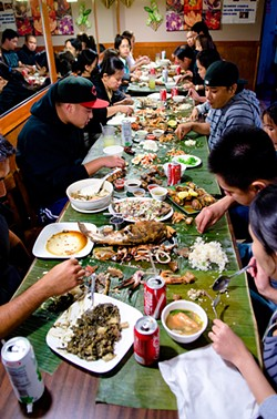 GIL RIEGO, JR. - An indoor Filipino picnic with rice, meats, and sauces, all for the grabbing.