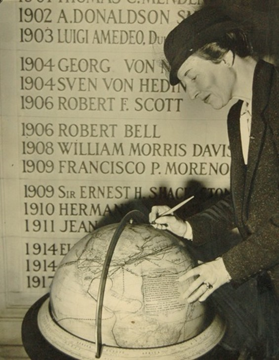 Boyd signing the globe at the American Geographical Society