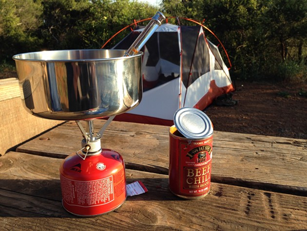 Camp Chili — Prep time: 30 sec— Cook time: 10 min — Serves 2 — Directions: Open two cans of chili, and empty into medium-sized pot. Light camp stove, place pot on top. Ignore precariousness of set-up, but try to remain alert so as to catch the pot if (when) it falls. Cook 10 minutes until lukewarm, or until stove runs out of fuel. Serve with potato chips and managed expectations. - PHOTO BY MIKE VANGEL