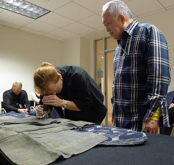 Curator Melissa Rinne  inspects a kimono brought in by Jaxon Nobori.