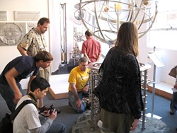 THE LONG NOW FOUNDATION - Curious onlookers gather around a planetary display.