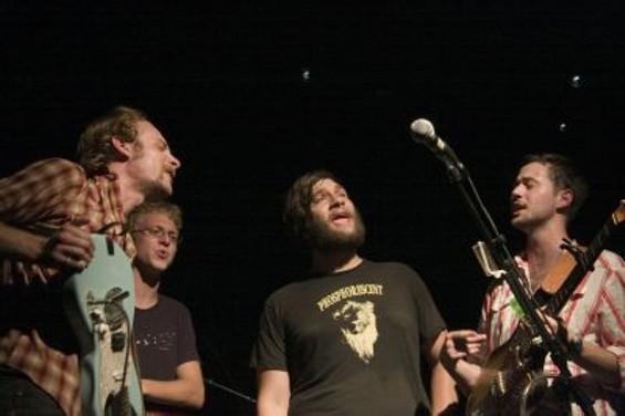 Deer Tick members gather around the mic to sing. - JOSEPH SCHELL