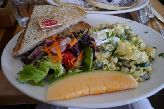 Farmer's scrambled eggs with vegetables, herbs and goat cheese, served with mixed greens and toast