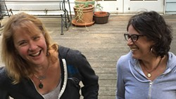 NOAH GOULD - Festival organizers Beth Gould and Elisabeth Pittinos share a laugh on a porch.