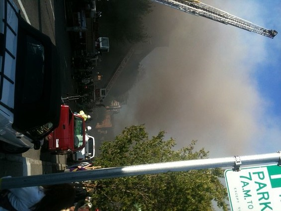 Flames are shooting through the roof of the burning structure... - JAKE SWEARINGEN