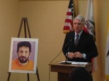 Gascon standing beside a mug shot of Reza Eslaminia. - ALBERT SAMAHA