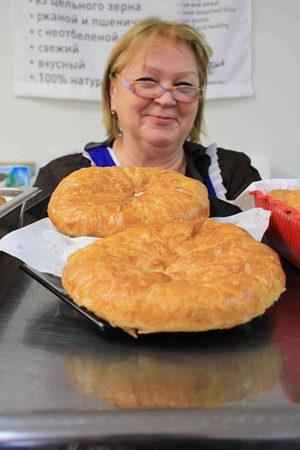 Gastronom's counter lady showing off the goods. - C. ALBURGER