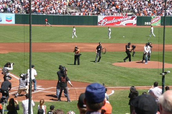 In a bit of role-reversal, former San Francisco 49ers receiver Jerry Rice throws to quarterback Steve Young for the ceremonial first pitch (high and outside) - ALL PHOTOS   |   TOM WALSH