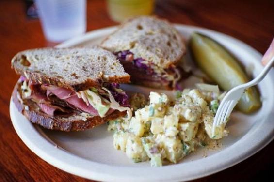 Jablow's pastrami sandwich with potato salad, and pickle. - JABLOW'S MEATS