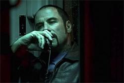 John Travolta plays the ringleader as a hair-triggered, showboating Joker.