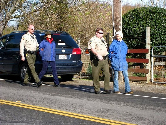 Katharina Sandizell-Smith, left, and Kristin McCrory are cuffed and taken into custody