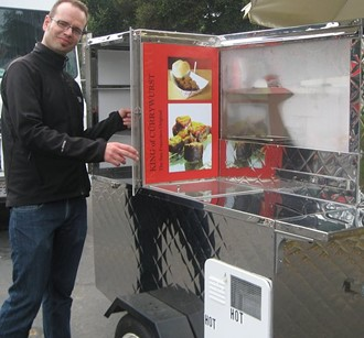 King of Cürrywurst's Dirk Adolphs, with the hot dog cart he plans to roll out daily at Divis and Fell.