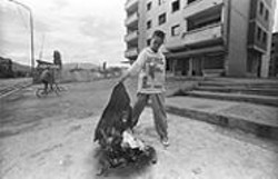 MARK  BRECKE - Kosovo, 1999: Kosovar Albanian boy - burning Serbian police uniforms.