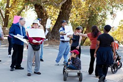 KIMBERLY SANDIE - Members of ASAN Sacramento hand out fliers to families walking for Autism Speaks. The walkers themselves have autistic children and friends, and ASAN hopes to convince them to support other groups