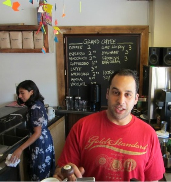 Nabeel Silmi makes a cappuccino while Bianca Solorzano tidies up