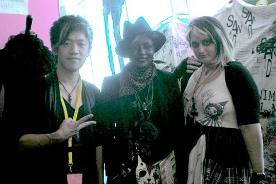 Naoto Hirooka stands with fans and aspiring designers Camille Tambe and Syu Martin.