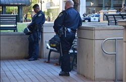 Oakland police wait for the action outside City Hall. - STEVE RHODES