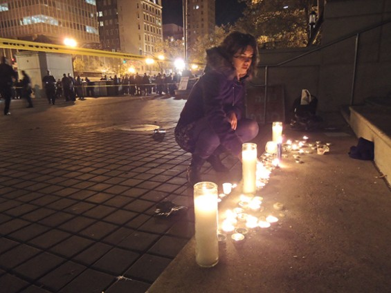 Occupy Oakland protester lights candles for the victim of last night's shooting in Frank Ogawa Plaza - KATE CONGER