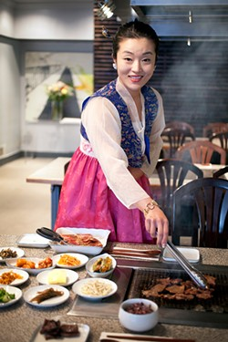 LARA HATA - Owner Ashley Lee, in traditional Korean dress, tends the grill.