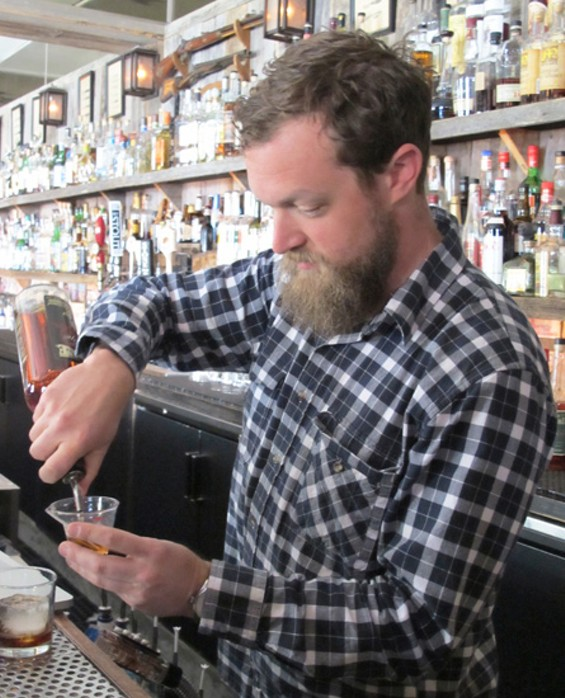 Owner Dylan O'Brien mixes a drink at Bloodhound. - LOU BUSTAMANTE