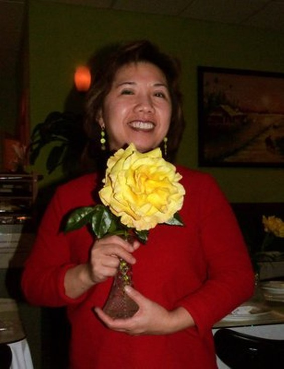 Owner Kathy Tang with a rose she grew. - YELP/ BOB L.