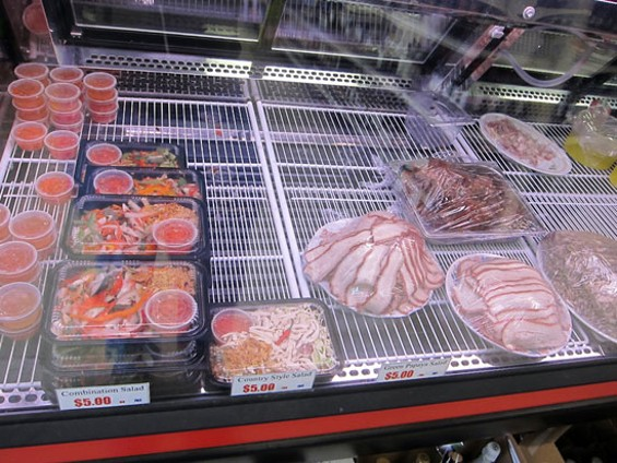 Packaged salads (left) and housemade cold cuts slices used for sandwiches (right) - LUIS CHONG