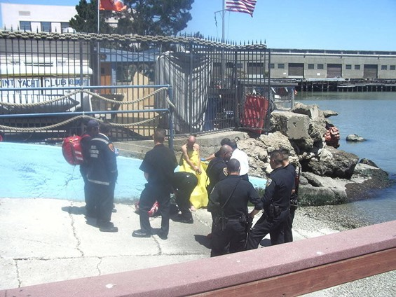Police converse with the man accused of attempting to steal a boat while clad only in a life vest. - DEANNA DESIN