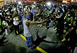 AP PHOTO/CHARLIE RIEDEL - Police draw guns on a man in Ferguson, Mo.